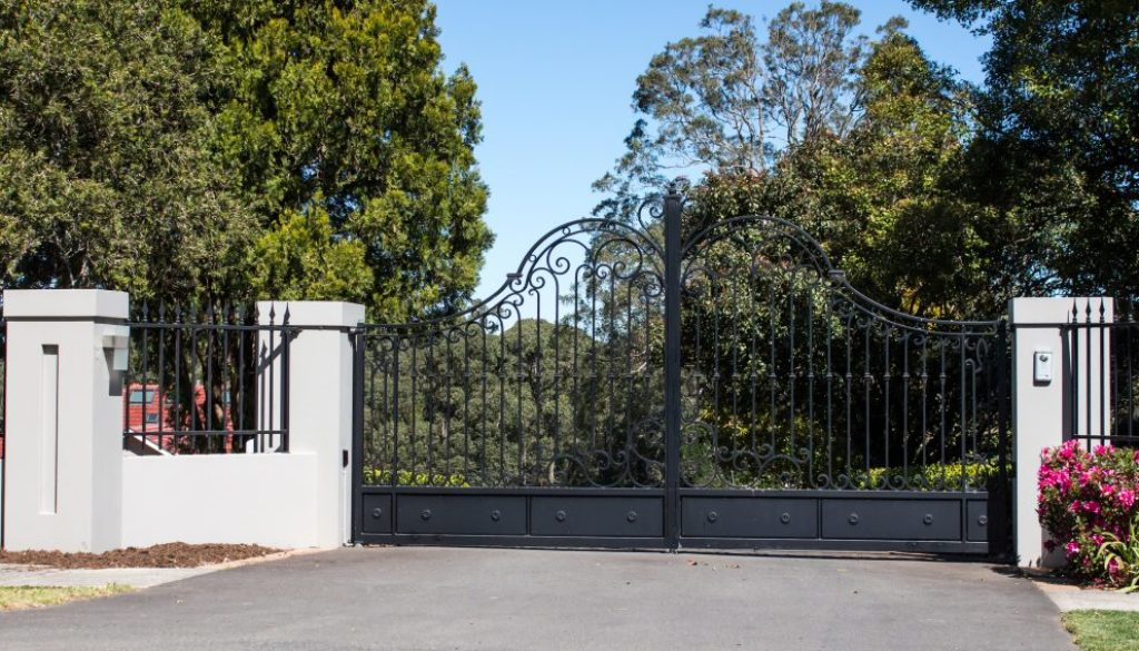 Metal Driveway Entrance Gates Set In Brick Fence With Garden Tre